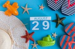 29. August Bild des vom 29. August Kalenders mit Sommerstrandzubehör und Reisendausstattung auf Hintergrund Baum auf dem Gebiet Lizenzfreies Stockbild