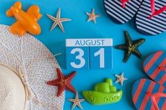 31. August Bild des vom 31. August Kalenders mit Sommerstrandzubehör und Reisendausstattung auf Hintergrund Baum auf dem Gebiet Stockfotografie
