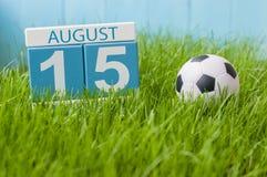 15. August Bild vom 15. August des hölzernen Farbkalenders auf Rasenhintergrund des grünen Grases mit Fußball Baum auf dem Gebiet Stockfotos