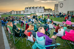 8 August, 2015, Crowds gather at De La Warr Pavilion for film show. People sitting on the grass in front of the De La Warr Pavilion building waiting for a summer royalty free stock photo