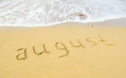 August - geschrieben in Sand auf Strandbeschaffenheit Stockbild