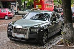 5. August 2012 Kiew, englisches Auto Rolls- Roycegeistes auf dem Hintergrund des britischen Busses Das Auto im Regen stockfoto