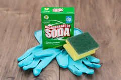 August 2nd, 2017, Cork, Ireland - a box of bicarbonate soda on top of a wooden table with a plastic scrubber, rubber gloves. August 2nd, 2017, Cork, Ireland - a stock photo