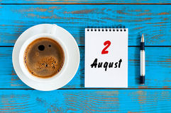 August 2nd. Day 2 of month, daily calendar on blue background with morning coffee cup. Summer time. Unique top view.  royalty free stock photos