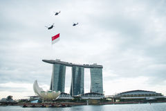 August 9, 2014: Singapore National Day. ,helicopter hanging Singapore flag flying over the Sands Hotel royalty free stock photography