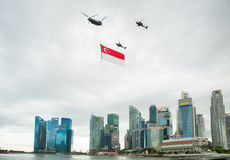 August 9, 2014: Singapore National Day. ,helicopter hanging Singapore flag flying over the Sands Hotel royalty free stock image