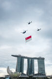 August 9, 2014: Singapore National Day. ,helicopter hanging Singapore flag flying over the Sands Hotel royalty free stock photos