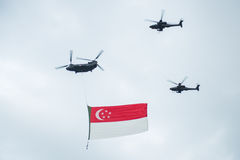 August 9, 2014: Singapore National Day. Ugust 9, 2014: Singapore National Day,helicopter hanging Singapore flag flying over the city royalty free stock images