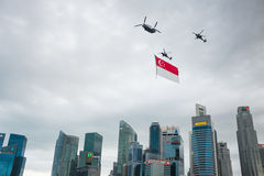 August 9, 2014: Singapore National Day. Ugust 9, 2014: Singapore National Day,helicopter hanging Singapore flag flying over the city stock image