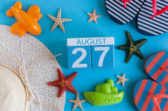 August 27th. Image of August 27 calendar with summer beach accessories and traveler outfit on background. Summer day. Vacation concept royalty free stock photo