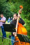 24 august 2017 Ukraine, White Church. A young musician with a beard playing a double bass in the park stock image