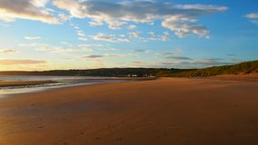 Sandy beach at dawn. August 2017: water breaks flat on the beach. The sun is rising to the east. August 2017 in Cullen Bay stock video