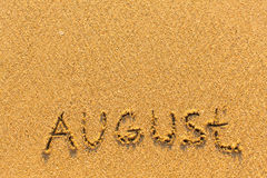 August - word inscription on the gold sand  beach. Royalty Free Stock Photos
