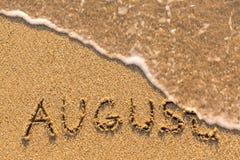 August - Wort gezeichnet auf den Sandstrand mit der weichen Welle Stockbilder