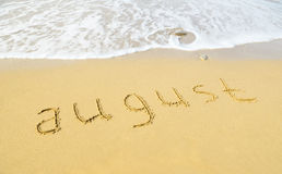 August - written in sand on beach texture Stock Image
