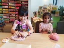 Augusti 14,2016 Bangkok i Thailand Thailändska flickor som sticker den woolen hatten hantverk och hobby för unge Royaltyfri Fotografi
