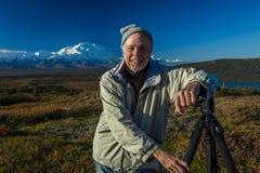 AUGUSTI 28, 2016 - fotografen Joe Sohm poserar på den berömda Ansel Adams bildfläcken, den mirakel- sjön, monteringen Denali, Kan Arkivfoto