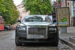 Augusti 5, 2012, Kiev, engelsk bil för Rolls Royce spöke på bakgrunden av den brittiska bussen Bilen i regnet arkivfoto