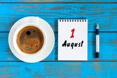 Augusti 1st dag 1 av månaden, lösblads- kalender på blå bakgrund med morgonkaffekoppen unga vuxen människa Unik bästa sikt Royaltyfria Bilder
