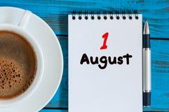 Augusti 1st dag 1 av månaden, lösblads- kalender på blå bakgrund med morgonkaffekoppen unga vuxen människa Unik bästa sikt Arkivfoton