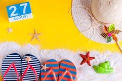 Augusti 27th Bilden av august kalender 27 med sommarstrandtillbehör och handelsresanden utrustar på bakgrund field treen Arkivbild