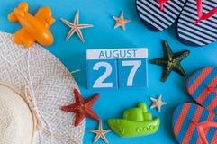 Augusti 27th Bilden av august kalender 27 med sommarstrandtillbehör och handelsresanden utrustar på bakgrund field treen Royaltyfri Foto