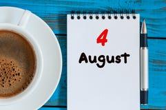 Augusti 4th Dag 4 av månaden, lösblads- kalender på blå bakgrund med morgonkaffekoppen unga vuxen människa Unik bästa sikt Royaltyfri Foto