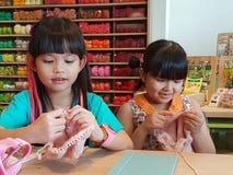 14,2016 augustus Bangkok in Thailand Thaise meisjes die wollen hoed breien ambacht en hobby voor jong geitje Royalty-vrije Stock Fotografie