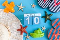 10 augustus Beeld van 10 augustus kalender met de toebehoren van het de zomerstrand en reizigersuitrusting op achtergrond Boom op Royalty-vrije Stock Foto