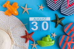 30 augustus Beeld van 30 Augustus kalender met de toebehoren van het de zomerstrand en reizigersuitrusting op achtergrond Boom op Stock Fotografie
