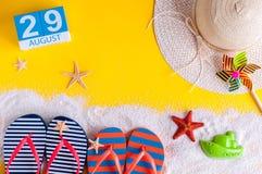 29 augustus Beeld van 29 Augustus kalender met de toebehoren van het de zomerstrand en reizigersuitrusting op achtergrond Boom op Stock Fotografie