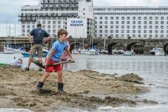 31 Augustus, 2014, Folkestone, Engeland, jongenskind graaft voor goud op strand Royalty-vrije Stock Foto