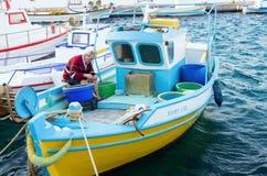 24 augustus 2017 - Leros eiland, Griekenland - een bejaarde visser werkt aan zijn netten in Leros eiland, Griekenland Stock Foto's