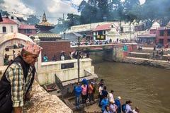 18 augustus, 2014 - Oude mens door een begrafenisbrandstapel in Katmandu, Nepal Stock Afbeeldingen