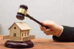 Auktion Real Estate begrepp Hand med domareauktionsklubban och husmodellen arkivfoto