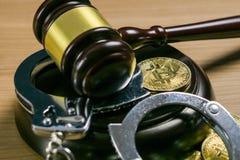 Auktionsklubba och handbojor med bitcoins på träskrivbordet Cryptocurrency lagligt begrepp arkivbilder