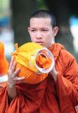 Aumône de marche de matin de jeunes moines asiatiques photo stock