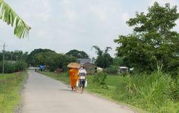 Aumône de marche de matin de jeunes moines asiatiques photographie stock libre de droits