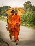 Aumône de marche de matin de jeunes moines asiatiques images libres de droits