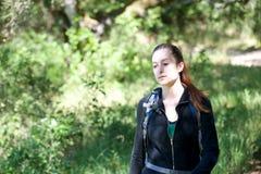 Aumenti della giovane donna attraverso la foresta ombreggiata immagini stock