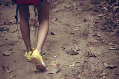 Aumenti e fine di viaggiatore con zaino e sacco a pelo sull'escursione delle scarpe della donna fotografia stock