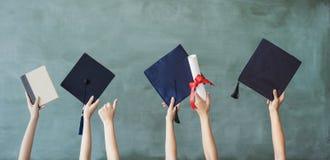Aumento de las manos con el casquillo de la graduación en el tablero de tiza fotos de archivo