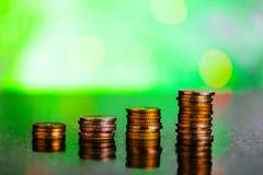 Aumento de las monedas en un fondo verde Imagen de archivo libre de regalías