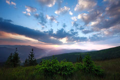 Aumento del sole di alba nelle prime ore del mattino in una valle della montagna fotografia stock