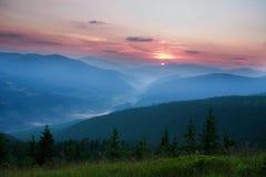 Aumento del sole di alba nelle prime ore del mattino in una valle della montagna Immagini Stock