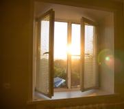 aumento del sole dietro i ciechi di finestra e le tonalità delle tende fotografia stock