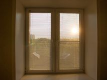 aumento del sole dietro i ciechi di finestra e le tonalità delle tende fotografie stock