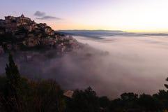 Aumento del villaggio della collina dalle nuvole Immagine Stock