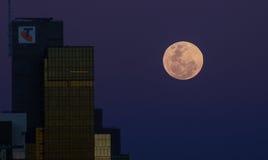 Aumento della luna piena vicino alle costruzioni moderne di CBD Fotografie Stock