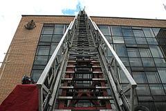 Aumento della scala del camion dei vigili del fuoco al tetto della casa Fotografia Stock